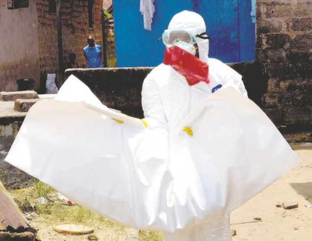 A Liberian Red Cross health worker, wearing a protective suit, carries the body of an 18-old-month baby, victim of the Ebola virus earlier this month in a district of Monrovia, the Liberian capital. (Zoom Dosso/AFP Photo)